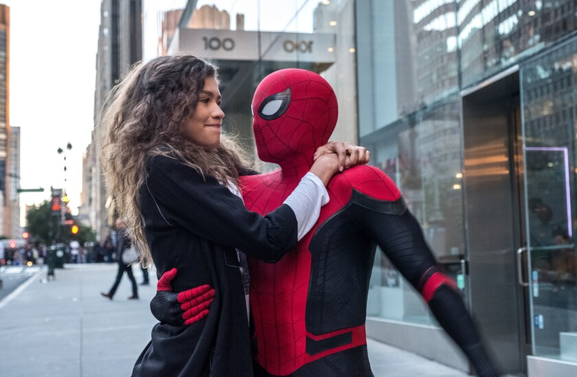A woman with long, brown hair hugging a man in a Spider-Man suit