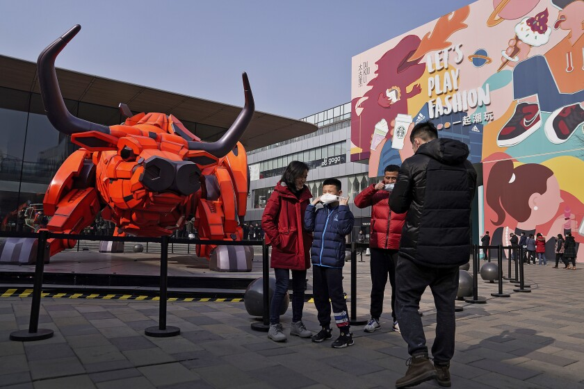 A man and a child put on their face mask to help curb the spread of the coronavirus after taken a souvenir photo near a Year of the Ox statue on display at the capital city's popular shopping mall during the first day of the Lunar New Year in Beijing, Friday, Feb. 12, 2021. Festivities for the holiday, normally East Asia's busiest tourism season, are muted after China, Vietnam, Taiwan and other governments tightened travel curbs and urged the public to avoid big gatherings following renewed virus outbreaks. (AP Photo/Andy Wong)