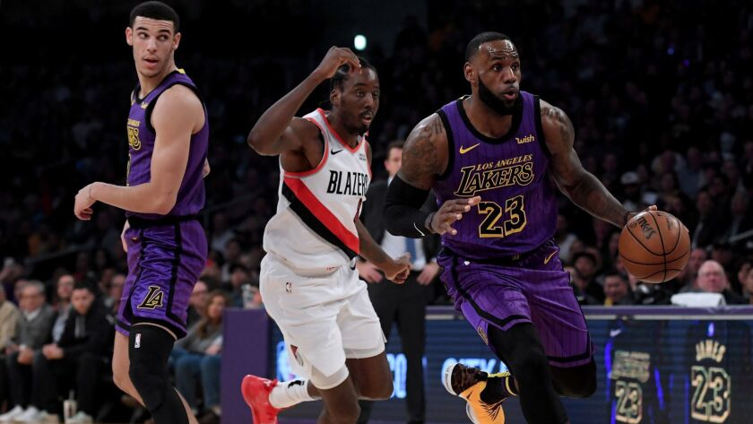Lakers forward LeBron James drives past Trail Blazers forward Al-Farouq Aminu after a screen by teammate Lonzo Ball during their game Nov. 14.