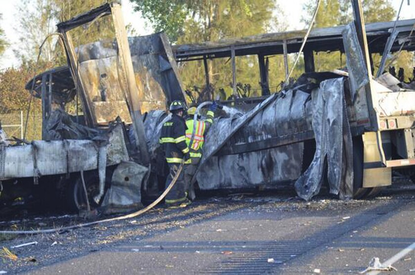 Firefighters hose down the wreckage of a bus and a truck that collided Thursday just north of Orland, Calif., killing at least nine people.