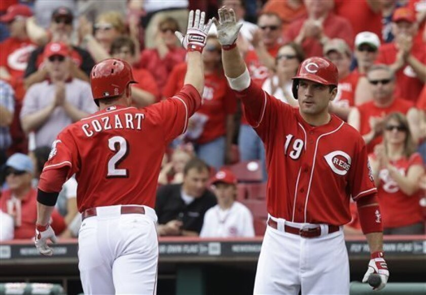 Cincinnati Reds' Zack Cozart (2) is congratulated by Joey Votto (19) after Cozart hit a home run off Atlanta Braves starting pitcher Mike Minor in the third inning of a baseball game, Wednesday, May 8, 2013, in Cincinnati. (AP Photo/Al Behrman)