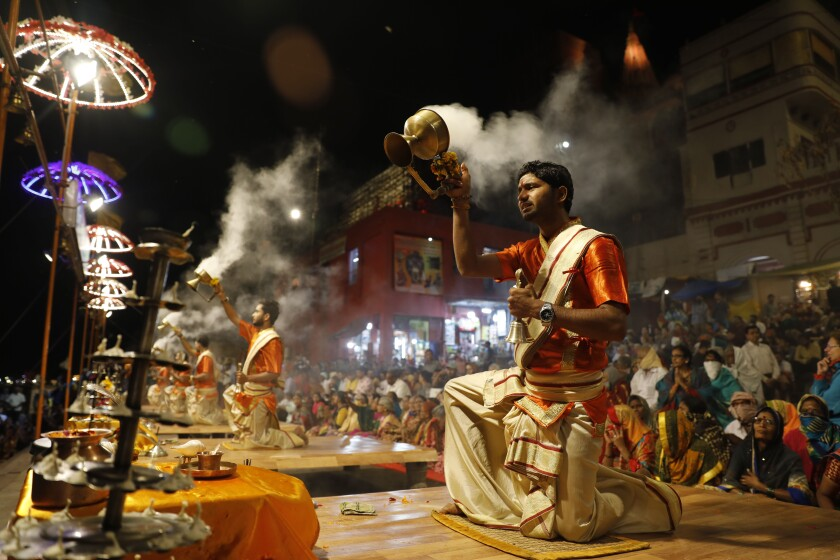 Hindu devotees watch as priests perform rituals during a prayer ceremony dedicated to holy river Ganges in Varanasi, India, Friday, March 6, 2020. India is bracing for a potential explosion of coronavirus cases as authorities rush to trace, test and quarantine contacts of 31 people confirmed to have the disease. Prime Minister Narendra Modi's government said last week that community transmission is now taking place. India has shut schools, stopped exporting key pharmaceutical ingredients and urged state governments to cancel public festivities for Holi, the Hindu springtime holiday in which people douse each other with colored water and paint. (AP Photo/Rajesh Kumar Singh)