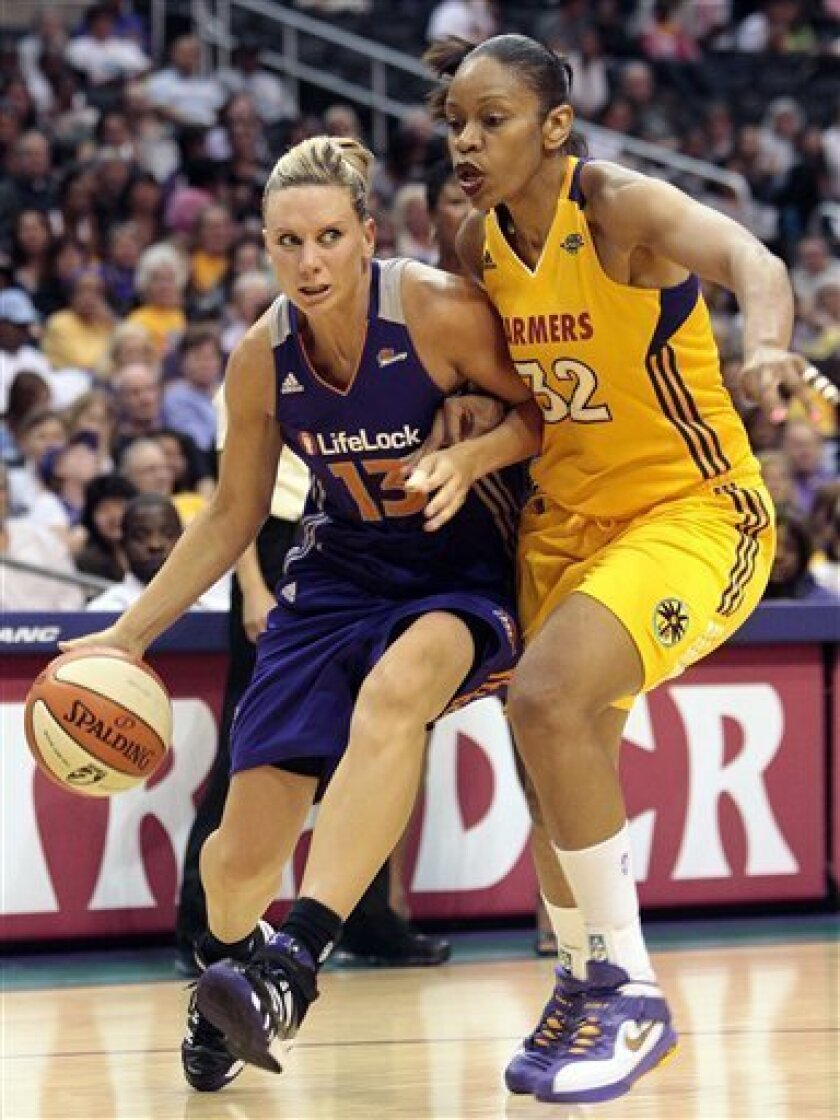 Phoenix Mercury forward Penny Taylor, left, of Australia drives to the basket as Los Angeles Sparks forward Tina Thompson defends during the first half of a WNBA basketball game in Los Angeles, Friday, June 10, 2011. (AP Photo/Jason Redmond)