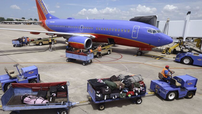 FILE - In this June 19, 2014 file photo, baggage carts are towed to a Southwest Airlines jet at Bill