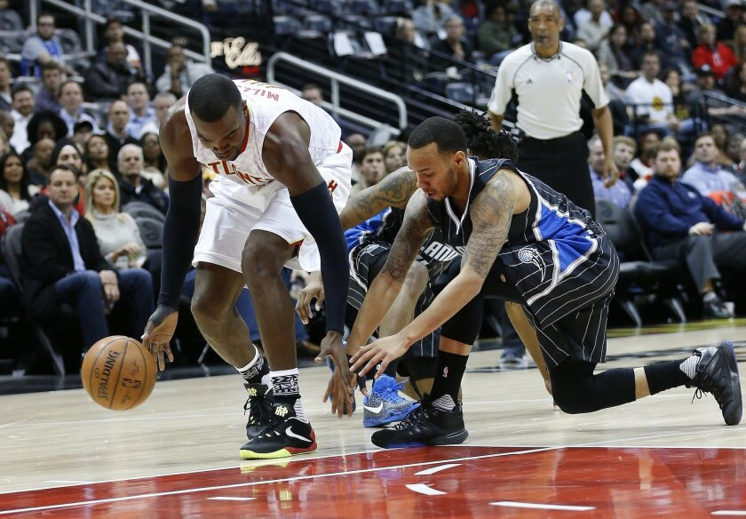 Atlanta Hawks forward Paul Millsap (4) and Orlando Magic guard Evan Fournier (10) vie for a loose ball in the first half of an NBA basketball game Monday, Feb. 8, 2016, in Atlanta. (AP Photo/John Bazemore)