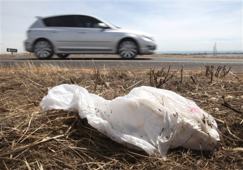 A car drives past a plastic bag lying on a on-ramp to Highway 70 near Olivehurs, Calif., Wednesday, June 2, 2010. The California Assembly on Wednesday passed legislation that would prohibit grocery stores, pharmacies, liquor stores and convenience stores from giving out free plastic and paper bags.