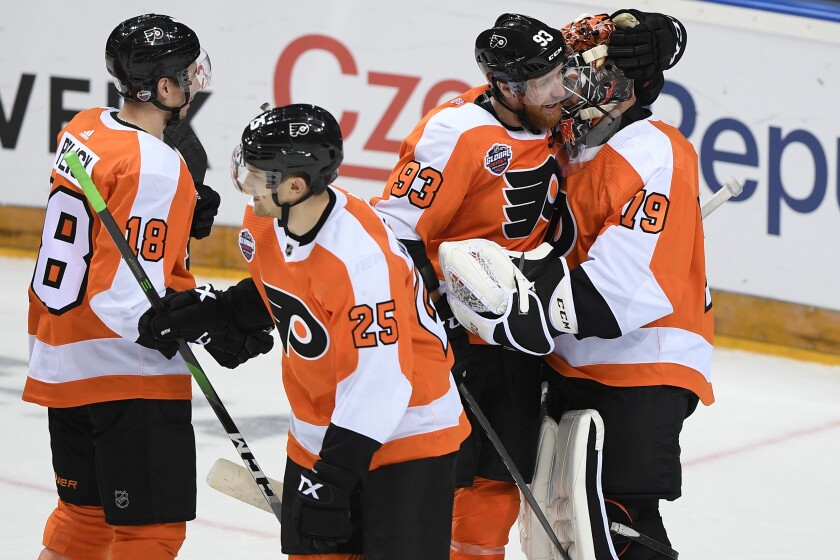 Philadelphia Flyers, from left, Tyler Pitlick, James van Riemsdyk, Jakub Voracek and Carter Hart, celebrate after they beat the Chicago Blackhawks 4-3 in an NHL Global Series ice hockey game in Prague, Czech Republic, Friday, Oct. 4, 2019. (Ondrej Deml/CTK via AP)