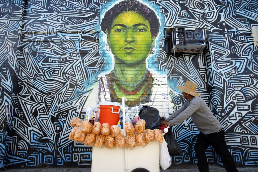 A street vendor pushes a cart past a mural of Frida Kahlo in Los Angeles.