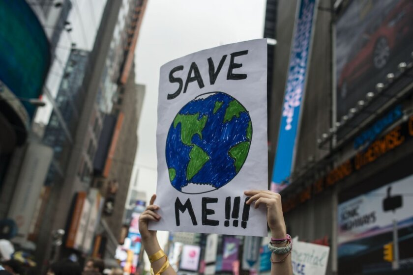 A demonstrator holds a sign during a climate rally