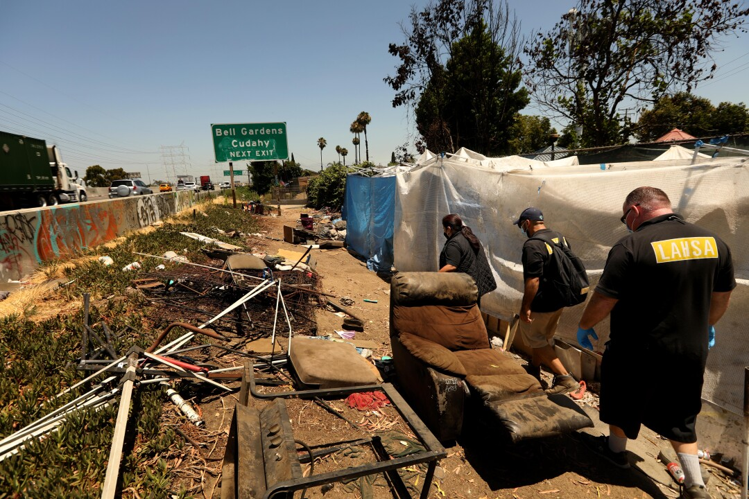 From right, John Oliver,  Jimmy Vasquez, Kim Barnett check on homeless encampments along the 710 in Bell Gardens.