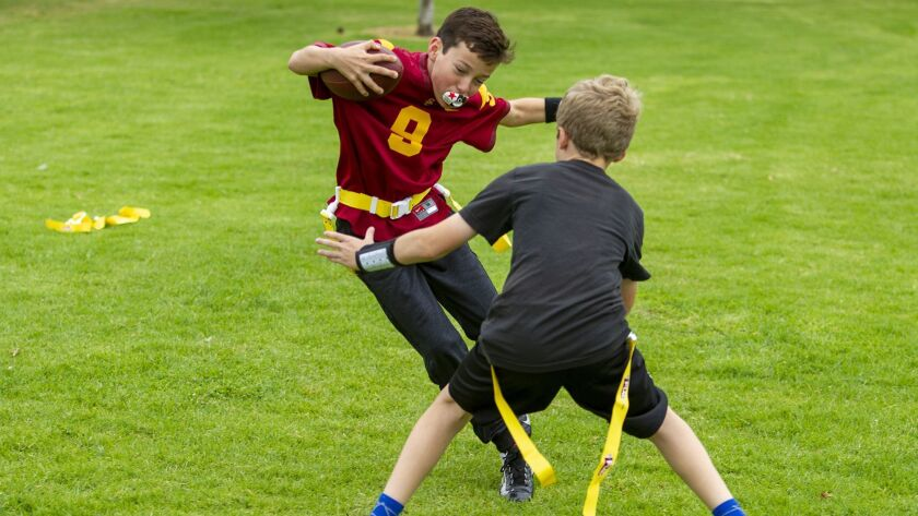 Jack Melenick, 11, left, attempts to avoid having his flag pulled by his teammate Ryan Pearson, 11,