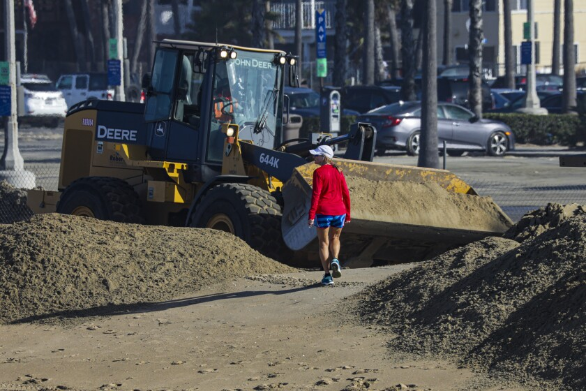 Bulldozers make sand berms near Balboa Pier.