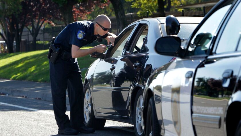 A Sacramento Police officer makes a traffic stop in November 2012. Gov. Jerry Brown signed a bill Tuesday to end the practice of Californians losing their driver's license because of unpaid traffic fines.