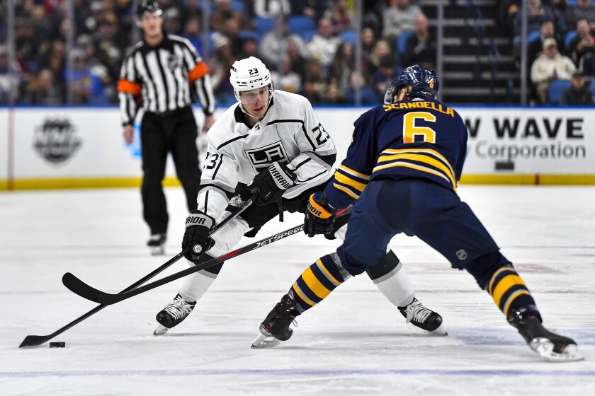 Kings right wing Dustin Brown works with the puck against Sabres defenseman Marco Scandella during the first period of a game Nov. 21.