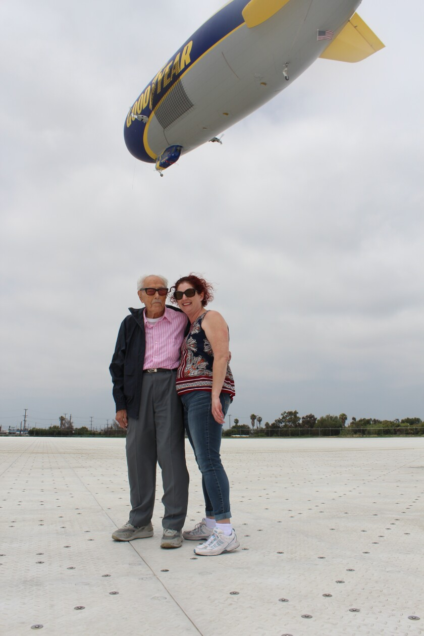 Glenn Quillin, 103, and his granddaughter Lisa Rhee pose for a photo after his June 7 flight on the Goodyear blimp Wingfoot Two, seen flying behind them in Gardena.