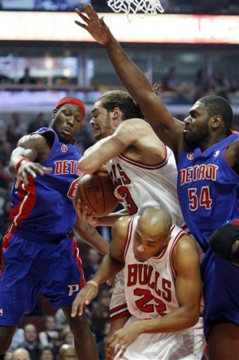 Chicago Bulls' Joakim Noah, center, battles for a rebound with Taj Gibson, bottom, and Detroit Pistons' Ben Wallace, left, and Jason Maxiell during the first quarter of an NBA basketball game in Chicago, Wednesday, Dec. 2, 2009.(AP Photo/Nam Y. Huh)