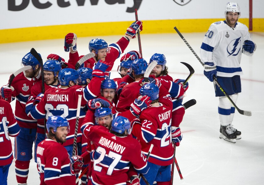 Tampa Bay Lightning's Blake Coleman (20) looks on as Montreal Canadiens celebrate teammate Josh Anderson's (17) winning goal at the end of overtime of Game 4 of the NHL hockey Stanley Cup final in Montreal, Monday, July 5, 2021. (Ryan Remiorz/The Canadian Press via AP)
