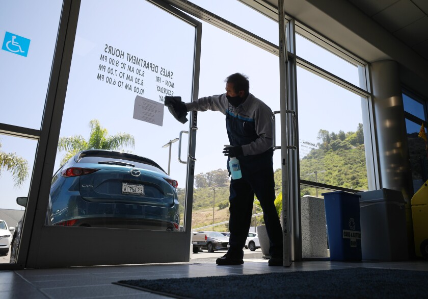 Rosendo Nevarez cleans a door at John Hine Mazda in Mission Valley.