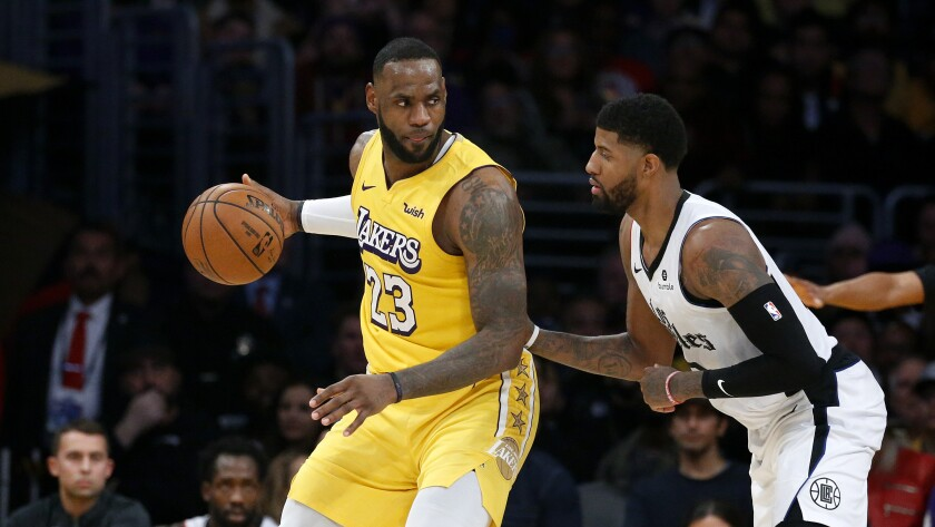 Lakers' LeBron James (23) is defended by Clippers' Paul George on Dec. 25, 2019, at Staples Center.