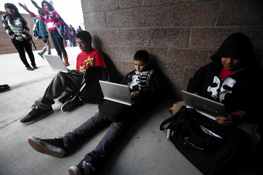 Perris middle school students Jacob Quinino, 13, left, Brian Guereque, 12, and Joshua Ortega, 12, use their Chromebooks during lunch break. The school district is paying about $344 for each device.