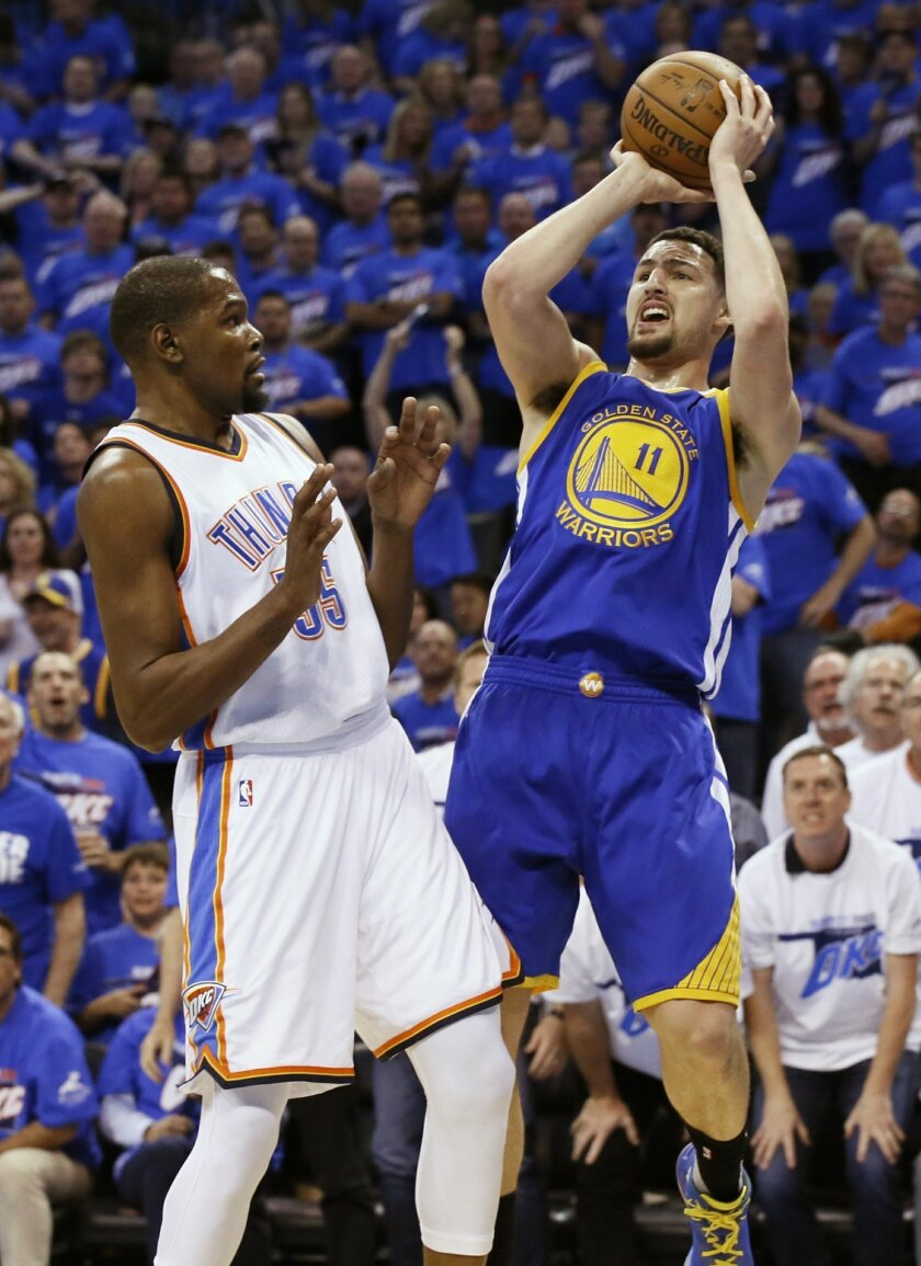 Golden State Warriors guard Klay Thompson (11) shoots as Oklahoma City Thunder forward Kevin Durant (35) defends during the first quarter in Game 3 of the NBA basketball Western Conference finals  in Oklahoma City, Sunday, May 22, 2016. (AP Photo/Sue Ogrocki)