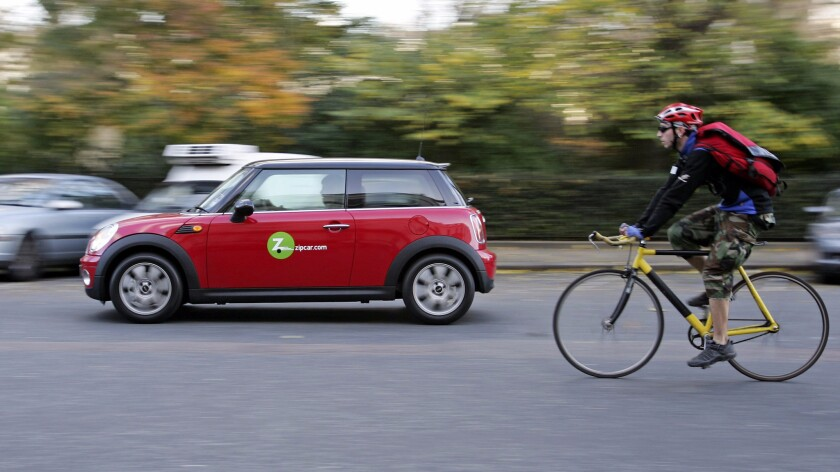 A rental car drives past a cyclist.