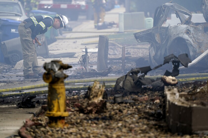 A fire official looks over the scene of a small plane crash.