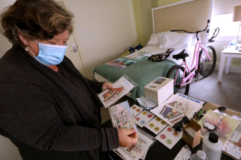 Artist Wendy Brown looks over her urban sketches in her hotel room.