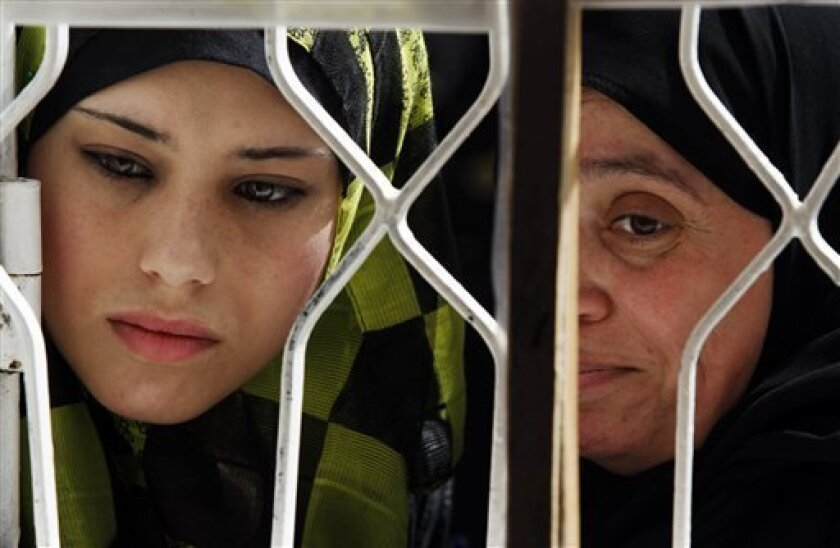 Members of a Palestinian family wait for their coupons to receive the monthly food supplies from the United Nations Relief and Works Agency, (UNRWA), at a warehouse in the Shatie refugee camp, in Gaza City, Sunday June 6, 2010. (AP Photo/Lefteris Pitarakis)