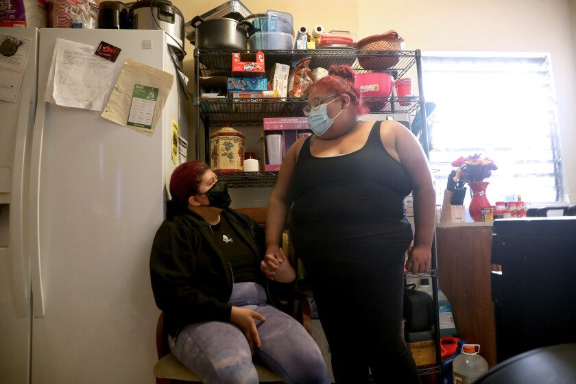 Two women, one seated, wear face masks as they hold hands near a refrigerator in a cramped apartment.