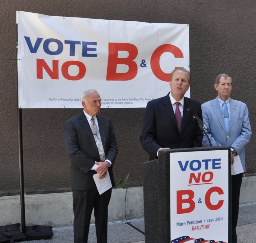 Mayor Kevin Faulconer talks about Propositions B and C related to the Barrio Logan community. At left is former Mayor Jerry Sanders and at right, Len Hering, a retired admiral who oversaw the San Diego naval command.