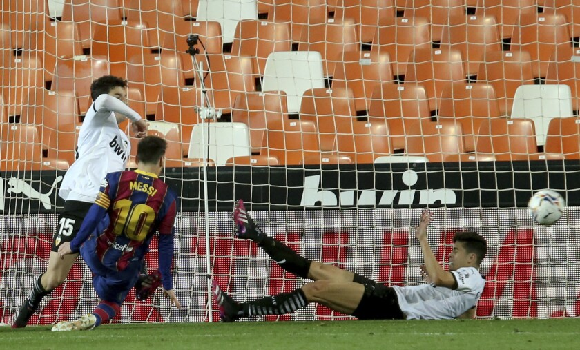 Barcelona's Lionel Messi scores his side's first goal during the Spanish La Liga soccer match between Valencia and Barcelona at the Mestalla stadium in Valencia, Spain, Sunday, May 2, 2021. (AP Photo/Alberto Saiz)