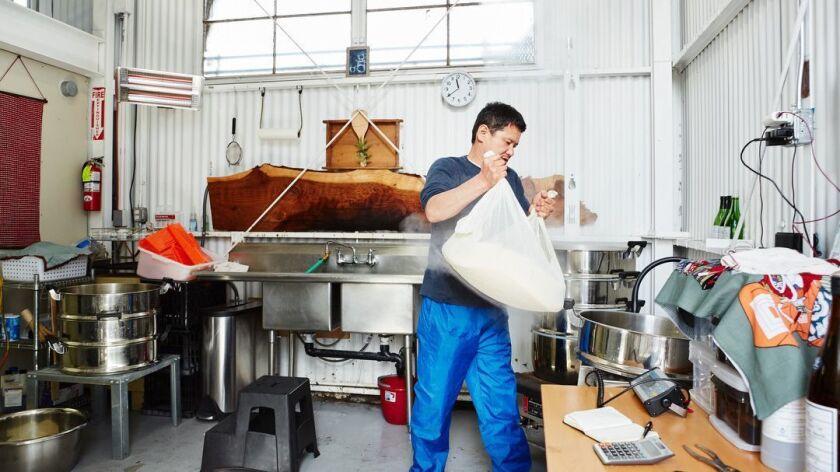 Oakland, CA - March 9, 2019: Yoshihiro Sako weighs steamed rice to brew sake at Den Sake Brewery. (C