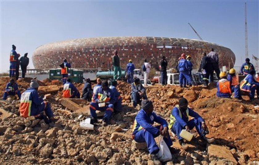 South African construction workers sit during their protest outside the Soccer City stadium on the outskirts of Soweto, South Africa, Wednesday July 8, 2009. South African construction workers at stadiums being built for the 2010 World Cup went on an indefinite strike Wednesday in a move which could derail next year's tournament. (AP Photo/Themba Hadebe)