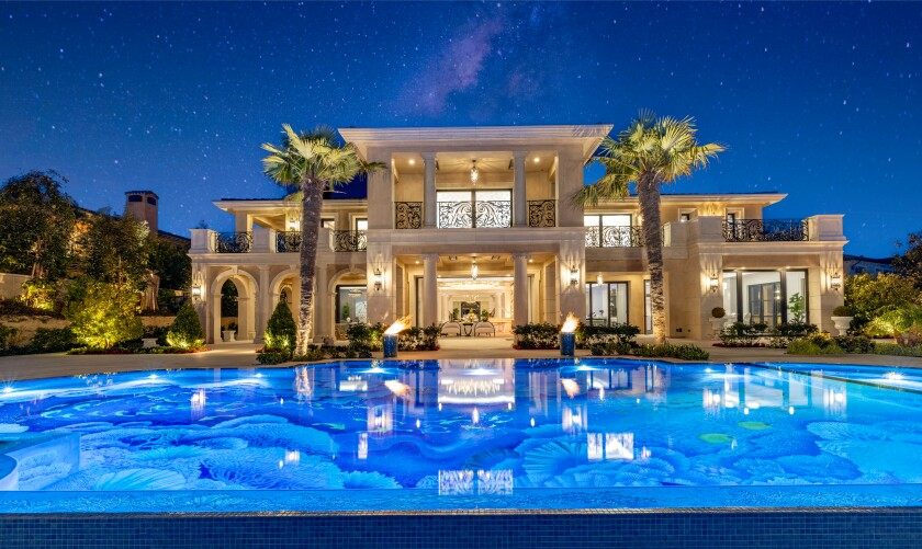 A mansion flanked by palm trees and a swimming pool