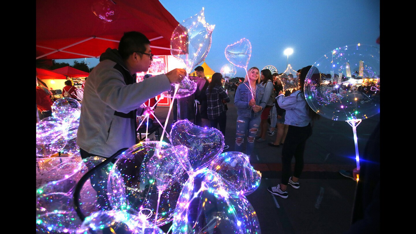 """Johnny Lin hands out """"bubble balloons"""" at dusk Friday during the OC Night Market at the OC Fair & Event Center in Costa Mesa. The market continues through Sunday."""