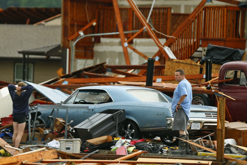 A man and woman inspect the damage to their home and classic cars after being hit by a tornado on Tu