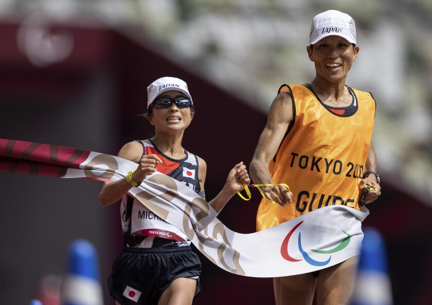 FILE - In this Sunday, Sept. 5, 2021, file photo, Misato Michishita, of Japan, and her guide break the tape to take the gold medal in the women's marathon T12 athletics final at the Tokyo 2020 Paralympic Games in Tokyo. The visually impaired Japanese office worker landed an invitation to compete in Monday's Boston Marathon, where she will be featured in a new para-athlete division being unveiled for the 125th edition of the race. (Simon Bruty for OIS via AP, File)