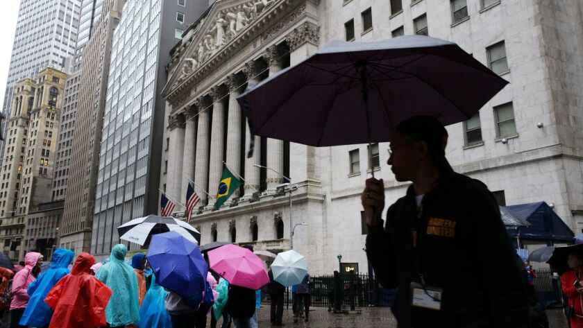 People carry umbrellas as they pass the New York Stock Exchange, Monday, May 13, 2019 in New York. U