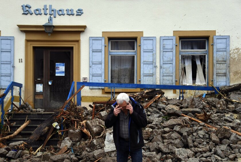 A man makes a phone call in front of an avalanche of debris that hit the town hall in Braunsbach, Germany, Monday, May 30, 2016. Authorities said three people are suspected to have died as floods struck Germany. Southern and western Germany, along with other parts of Europe, experienced heavy rainstorms over the weekend. (Marijan Murat/dpa via AP)