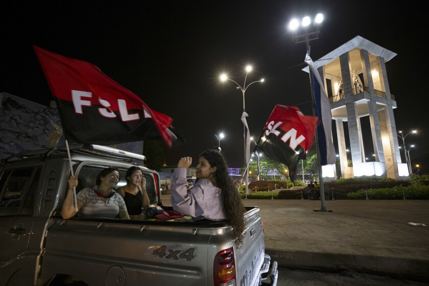 Women wave Sandinista National Liberation Front (FSLN) flags during commemorations for the 42nd anniversary of the triumph of the 1979 Sandinista Revolution that toppled dictator Anastasio Somoza in Managua, Nicaragua, Sunday, July 18, 2021. (AP Photo/Miguel Andrés)