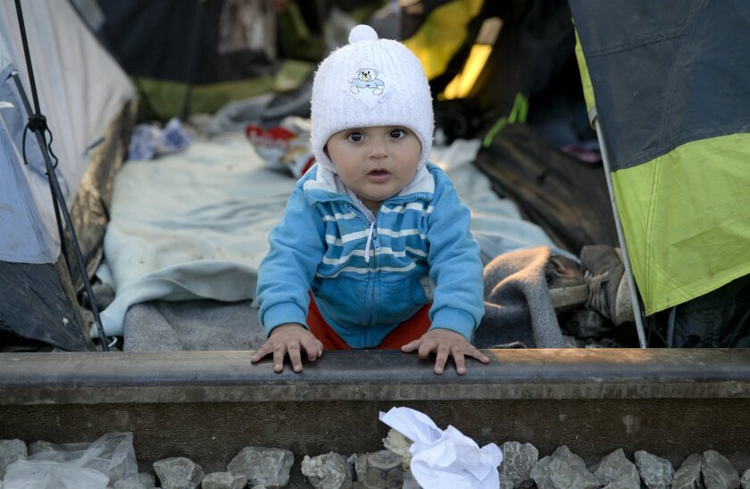 A baby leans on the railway tracks at the northern Greek border point of Idomeni, Greece, Saturday, March 19, 2016. German Chancellor Angela Merkel is urging migrants in the squalid tent city at Idomeni, on the Greek-Macedonian border, to trust Greek authorities and leave for better accommodation a