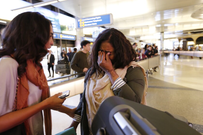 Abeer Abdelrahman, left, comforts her crying sister Areej Ali at Los Angeles International Airport on Monday. Ali was detained after arriving from Sudan.