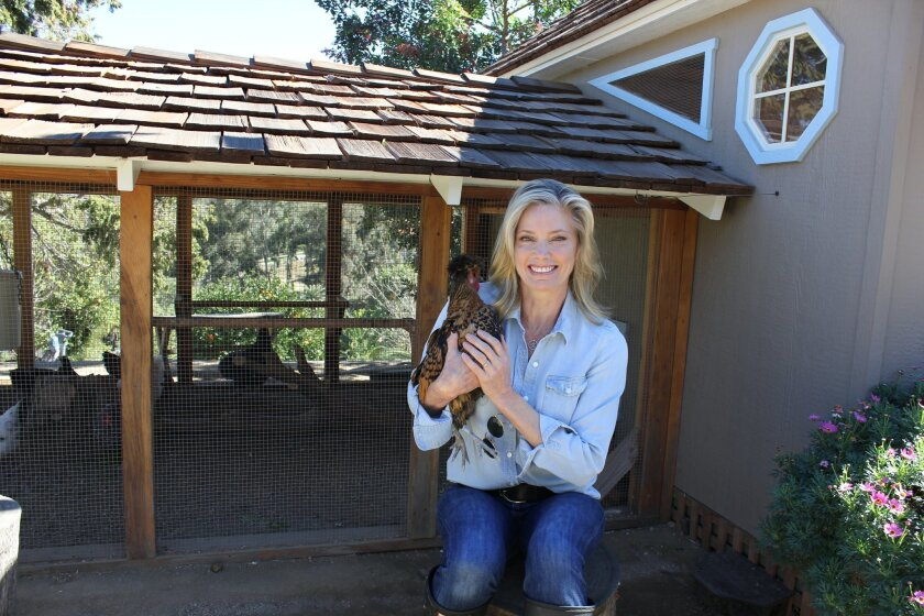 Kelly Emberg holding one of her chickens, seated in front of her chicken coop and screened-in chicken run.