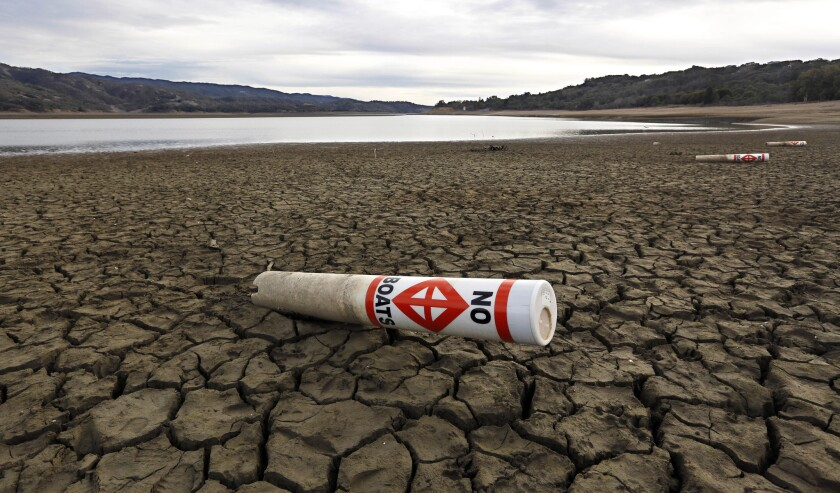 In this February 2014 photo, a warning buoy sits on the dry, cracked bed of Lake Mendocino near Ukiah, Calif.