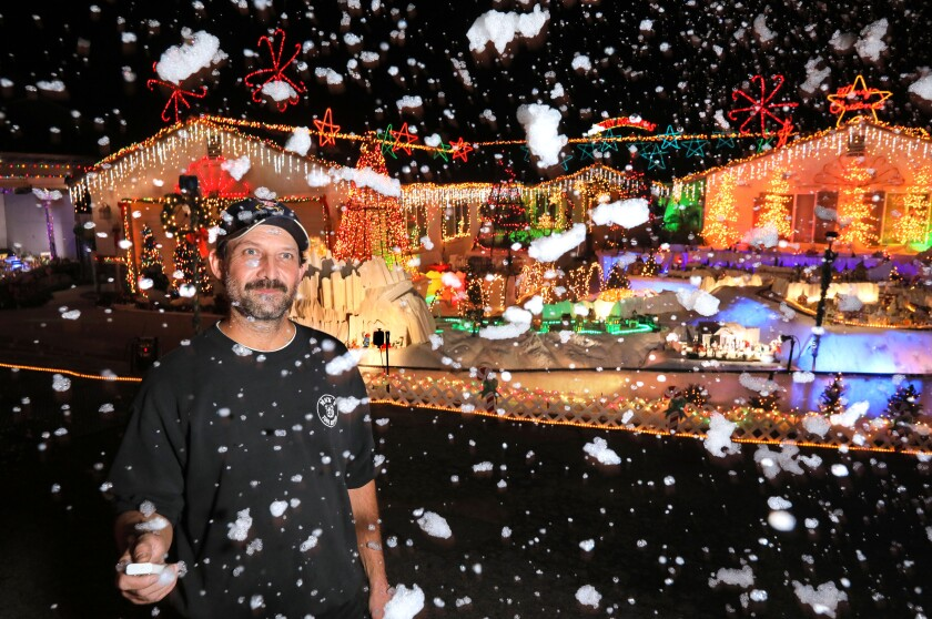 Mack Schreiber stands in a flurry of man-made snow in front of his Fallbrook home, which draws 18,000 visitors each holiday season.