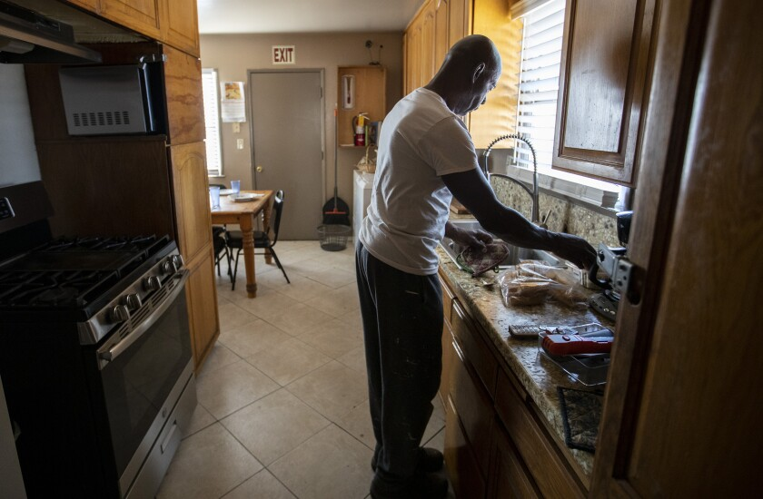 Sam Blake cleans up in the kitchen of the Blake Home, a board-and-care facility in Sylmar.