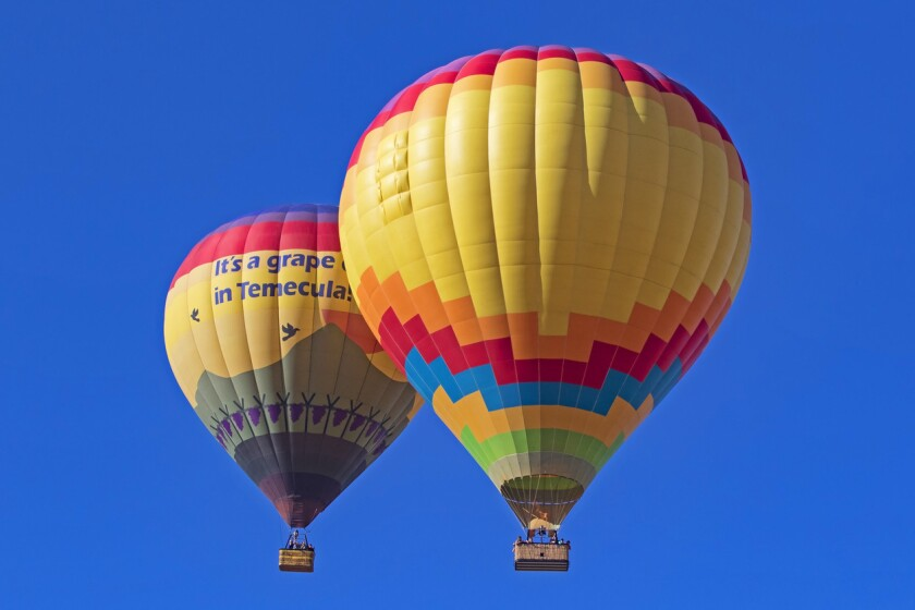Hot air balloons flying over California winery and grape vineyards during 2017 Temecula Balloon and Wine Festival in Southern California.