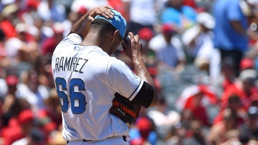 JC Ramirez adjusts his hat while standing on the mound during the third inning of the Angels' 7-3 lo