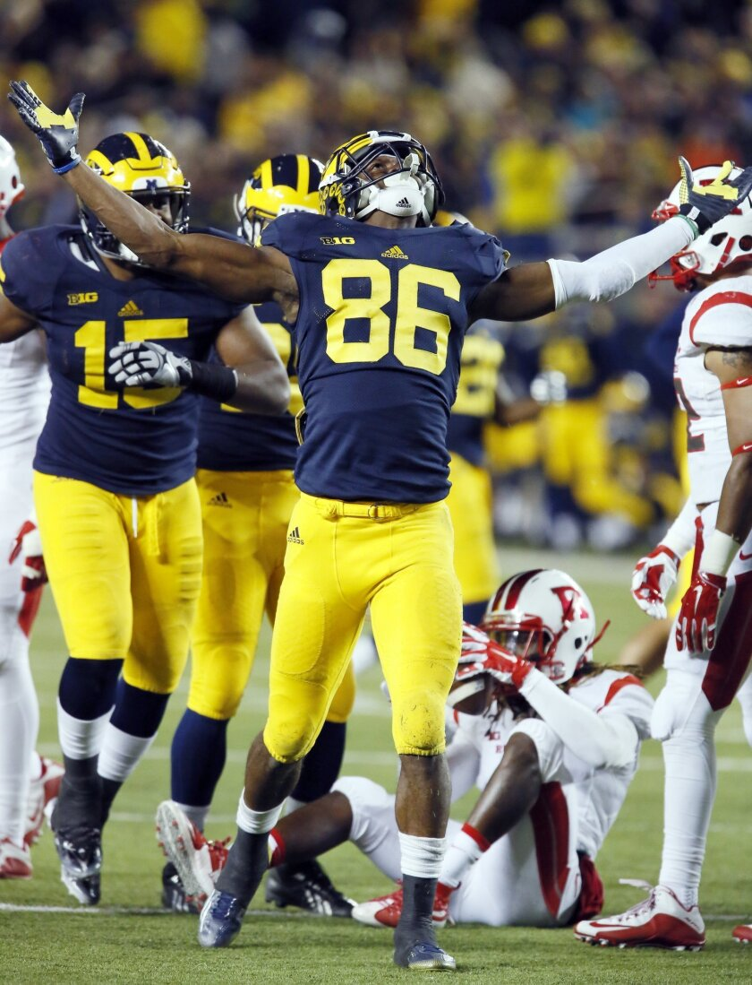 Michigan's Jehu Chesson (86) celebrates after tackling  Rutgers' Janarion Grant, bottom, behind the line of scrimmage during the second half of an NCAA college football game Saturday, Nov. 7, 2015, in Ann Arbor, Mich. Michigan defeated Rutgers 49-16. (AP Photo/Duane Burleson)